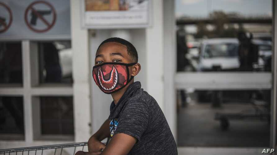 TOPSHOT - A boy wears a face mask as a preventive measure against the spred of the COVID-19 coronavirus as he queues outside…