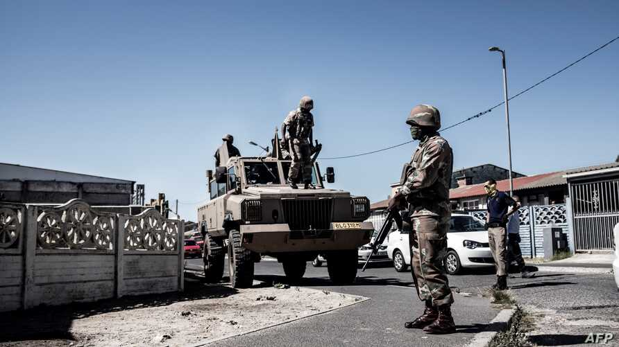 South African National Defence Force (SANDF) soldiers stand next to an Armoured Personnel Carrier (APC) in the Cape Flats area…
