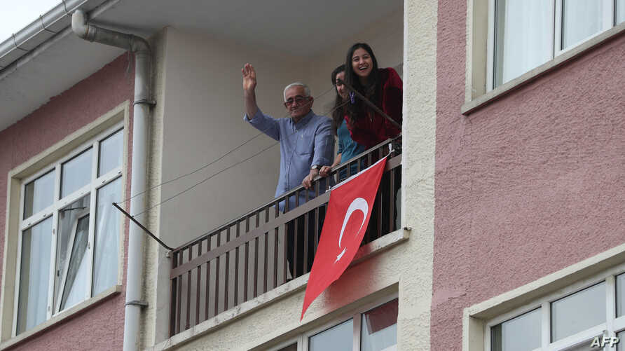 Residents wave from their balcony as they attend a concert by artists from the Kecioren municipality conservatory performing…