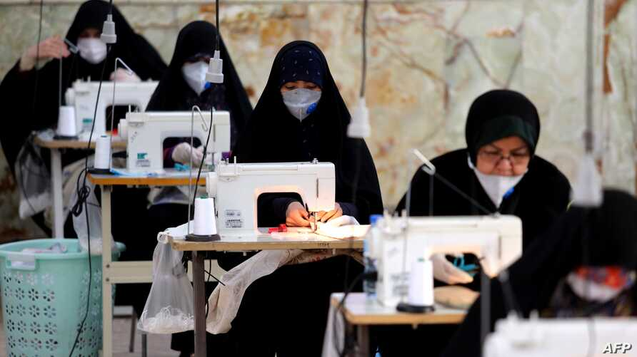 TOPSHOT - Iranian women, members of paramilitary organisation Basij,  make face masks and other protective items at a mosque in…