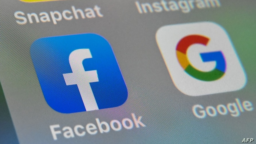 (FILES) This file picture taken on October 1, 2019 shows the logos of mobile apps Facebook and Google displayed on a tablet in…