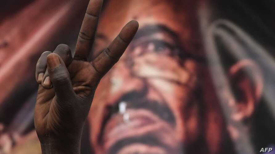 (FILES) In this file photo taken on April 19, 2019, a Sudanese protester flashes a victory sign in front of a banner depicting…
