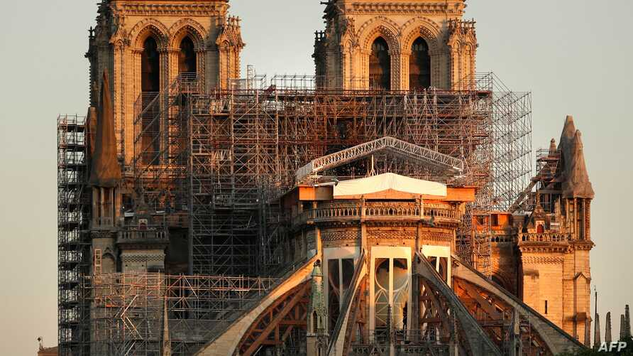 This picture taken on April 14, 2020 shows the Paris' Cathedral Notre Dame at the sunrise on the eve of the first anniversary…