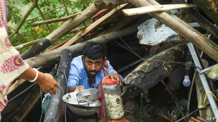 Villagers salvage items from their house damaged by cyclone Amphan in Midnapore, West Bengal, on May 21, 2020. - The strongest…
