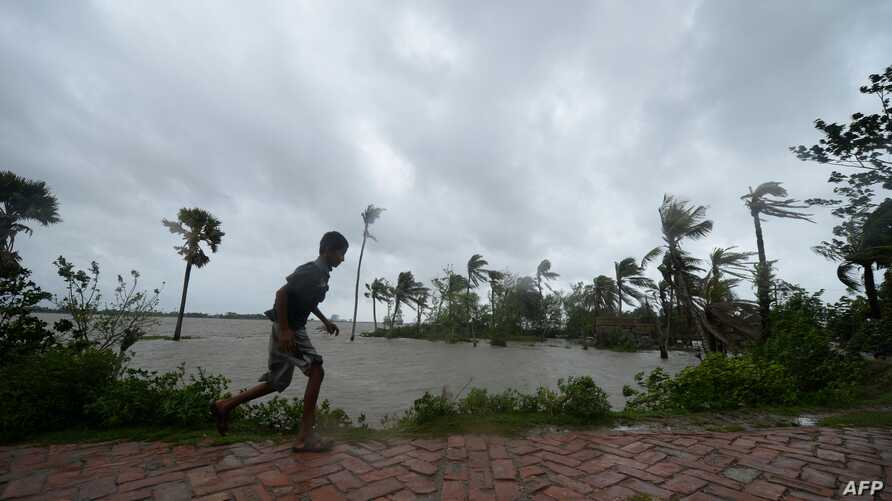 TOPSHOT - A boy runs along an embankment ahead of the expected landfall of cyclone Amphan, in Dacope on May 20, 2020. - Several…