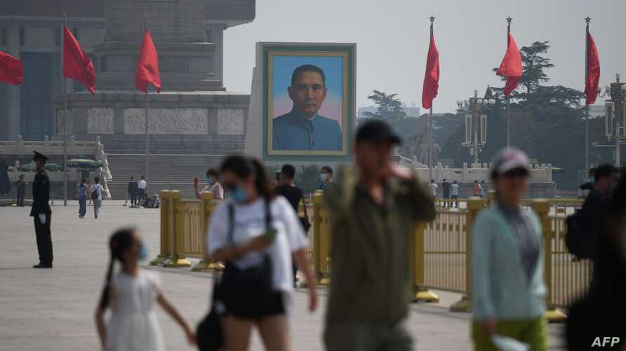 Visitors walk near a portrait of Sun Yat-sen, the first provisional president of the Republic of China, in Beijing's Tiananmen…