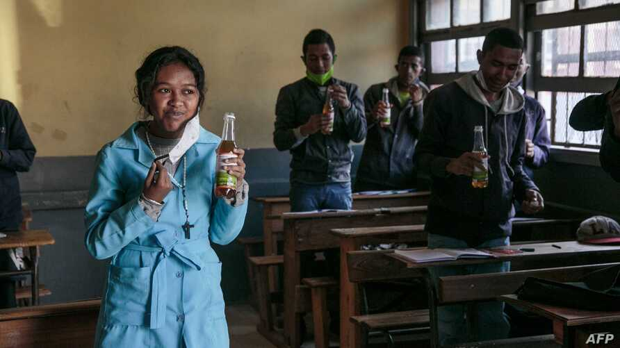 Students drink from bottles of Covid Organics, a herbal tea, touted by Madagascar President Andry Rajoelina as a powerful…