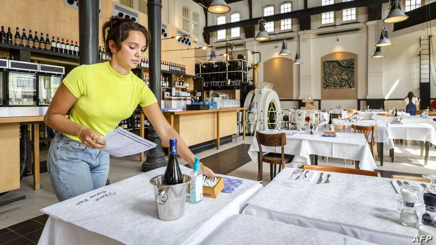 An employee prepares a cafe-restaurant for the reopening in Amsterdam, The Netherlands, on May 26, 2020, during the ongoing…
