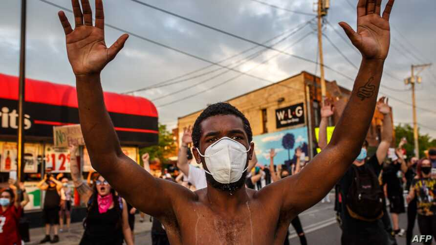TOPSHOT - A protester wearing a facemask holds up his hands during a demonstration over the killing of George Floyd by a…