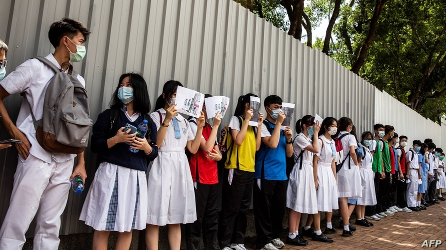 School students hold signs during a pro-democracy protests near their school in Hong Kong on June 12, 2020. (Photo by ISAAC…