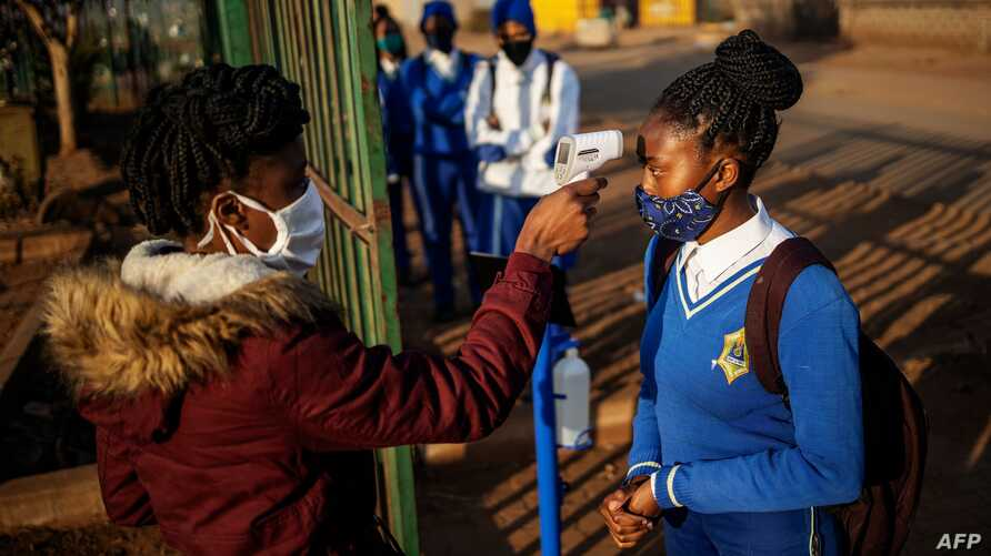 A pupil at the Winnie Mandela Secondary School has her temperature measured as she enters the school premises before classes…