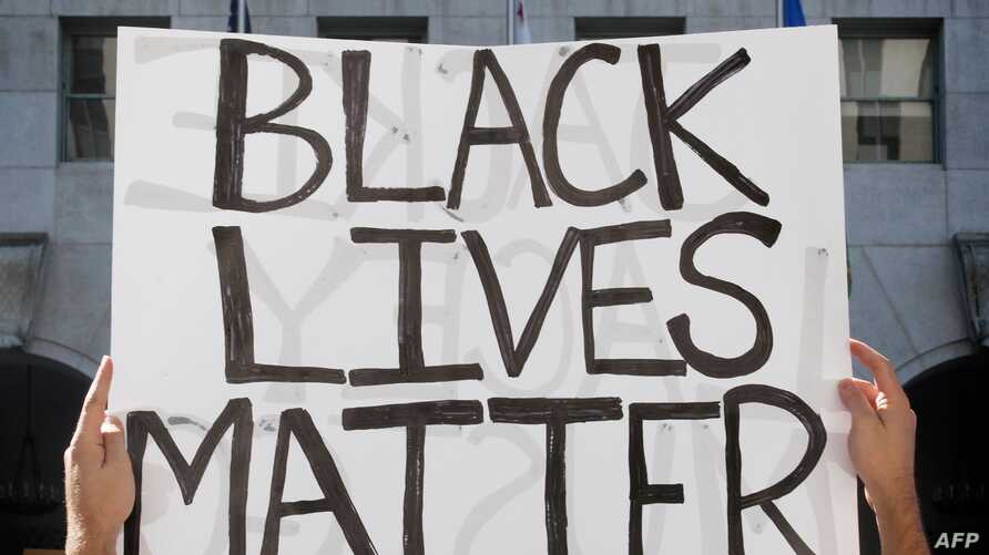 A supporter of Black Lives Matter, holds a sign during a protest outside the Hall of Justice as they demonstrate against the…