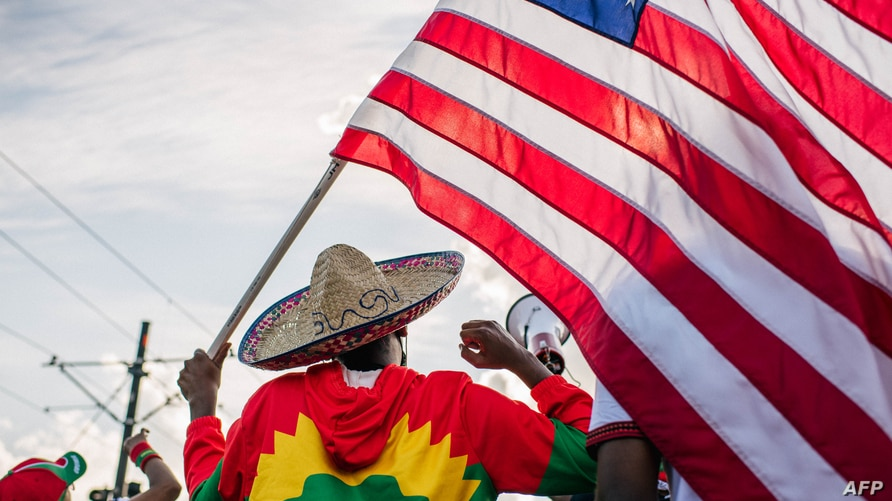 ST. PAUL, MN - JULY 08: A man holds up the U.S. flag as members of the Oromo community march in protest over the death of…