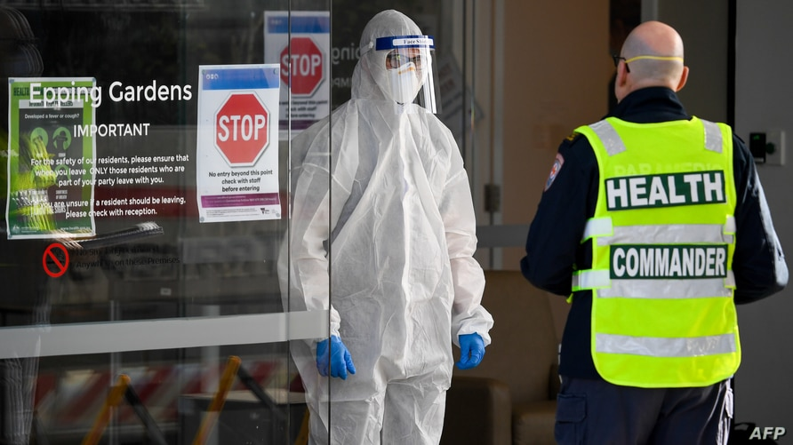 Medical workers speak at the entrance of the Epping Gardens aged care facility in the Melbourne suburb of Epping on July 29,…