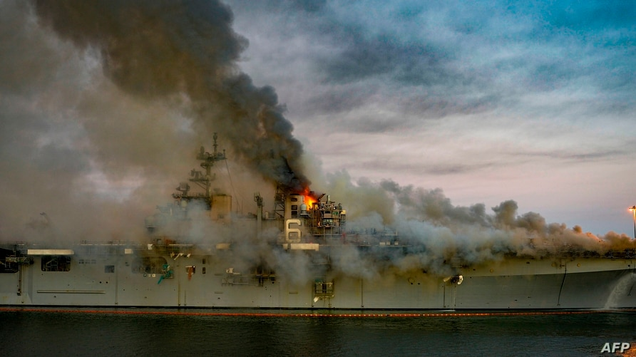 This US Navy photo released July 13, 2020 shows a fire as it continues to be fought into the evening on board the amphibious…