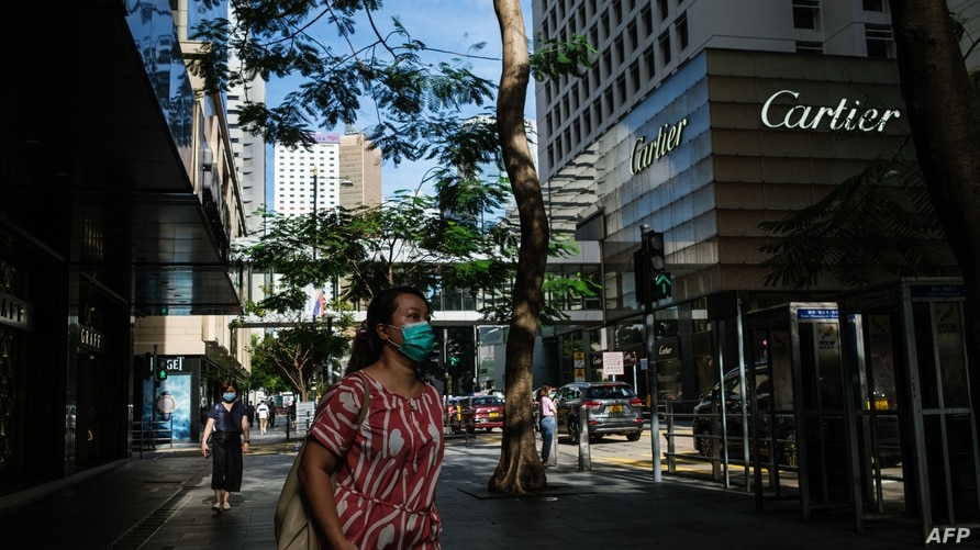 Pedestrians wear face masks as they walk on a pavement past high end fashion shops in the Central district of Hong Kong on July…