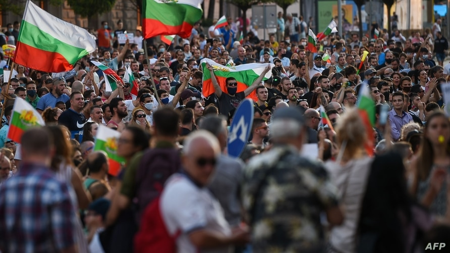 Protestors shout slogans and wave Bulgarian national flags during an anti-government protest in Sofia, on July 11, 2020. - The…