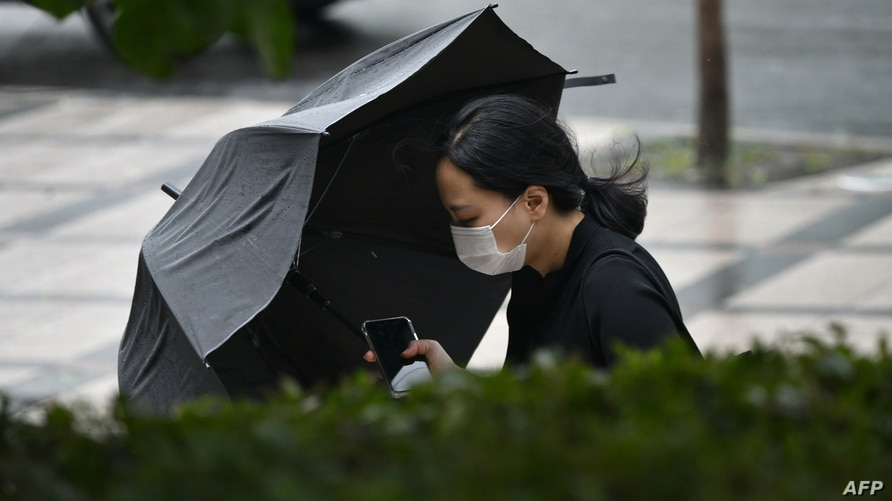 A woman holding her umbrella walks in strong winds in Seoul on August 27, 2020 after Typhoon Bavi hit the Korean Peninsula. -…