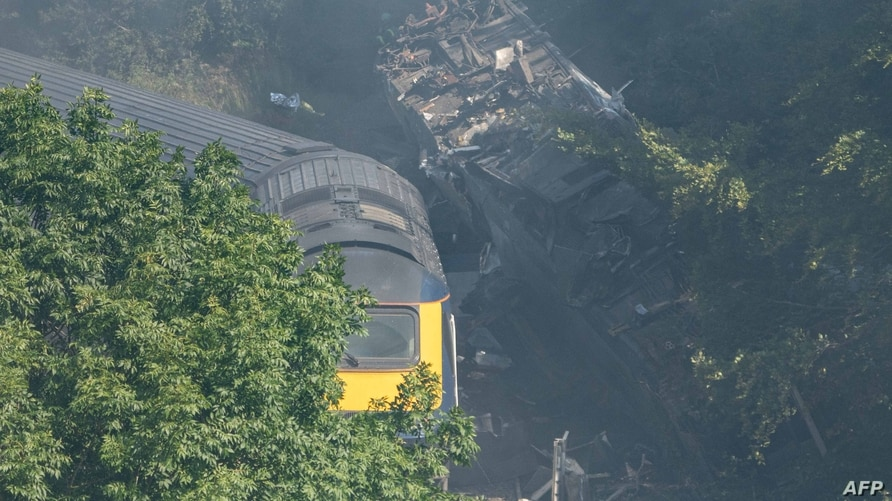 Derailed carriages are seen at the scene of a train crash near Stonehaven in northeast Scotland on August 12, 2020. - Three…