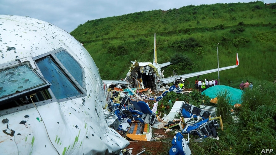Officials inspect the wreckage of an Air India Express jet at Calicut International Airport in Karipur, Kerala, on August 8,…