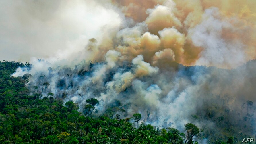 (FILES) In this file photo taken on August 16, 2020, aerial view of a burning area of Amazon rainforest reserve, south of Novo…