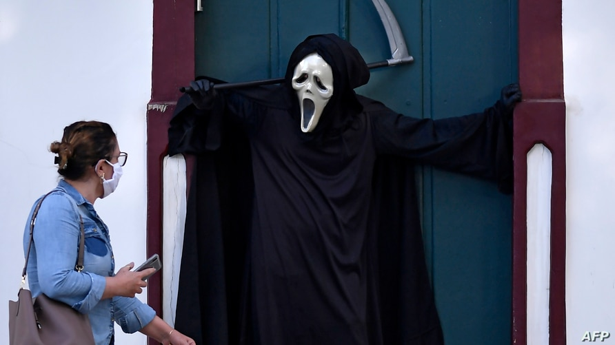 TOPSHOT - A woman looks at Brazilian actor Fabio de Almeida disguised as death to raise awareness of the importance of wearing…