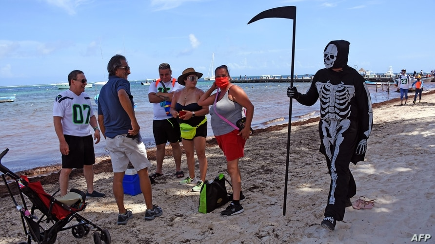 A young man disguised as the death walks at the beach of Puerto Morelos inviting tourists and locals to return to their homes …