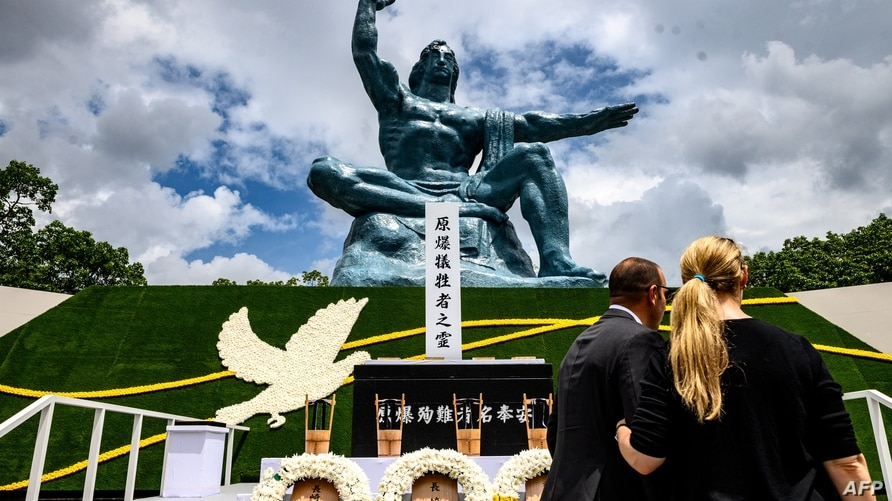 People stand in front of the cenotaph and the Peace statue after the ceremony marking the 75th anniversary of the atomic…