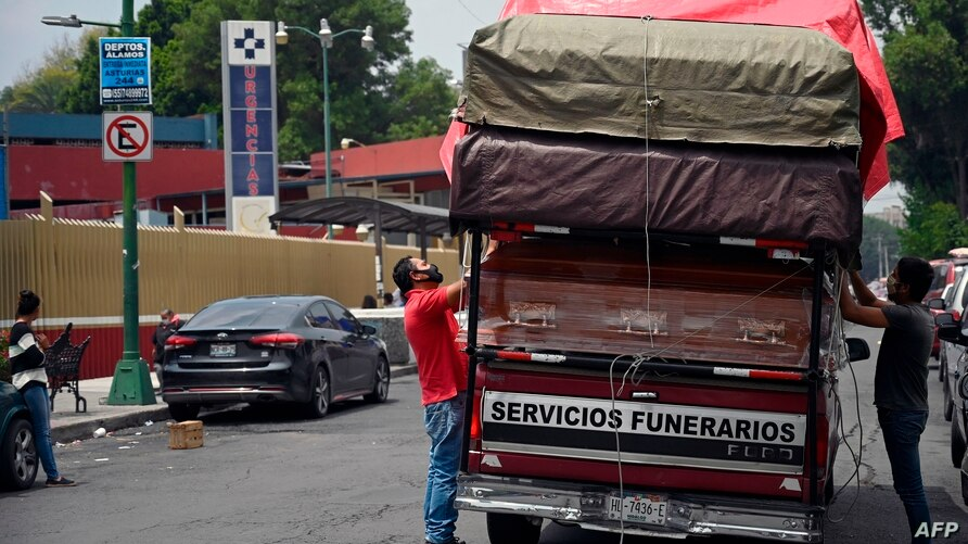 Workers unload coffins from a truck outside a funeral home located in front of the General Hospital in Mexico City on August 20…