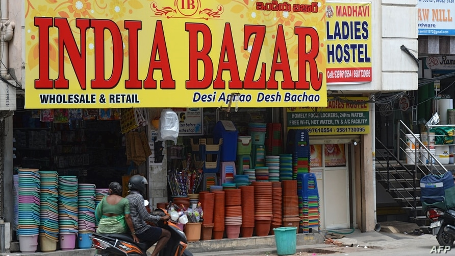 Commuters on a scooter ride past a shop whose name was changed from 'China Bazar' to 'India Bazar' in Hyderabad on September 10…