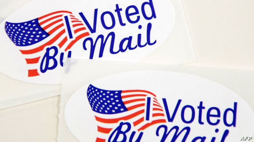 """TOPSHOT - Stickers that read """"I Voted By Mail"""" sit on a table waiting to be stuffed into envelopes by absentee ballot election…"""