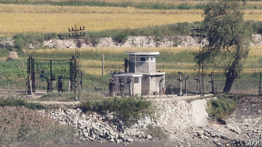 North Korean soldiers are seen at a military fence next to a guard post in the North Korean border county of Kaepoong, as seen…