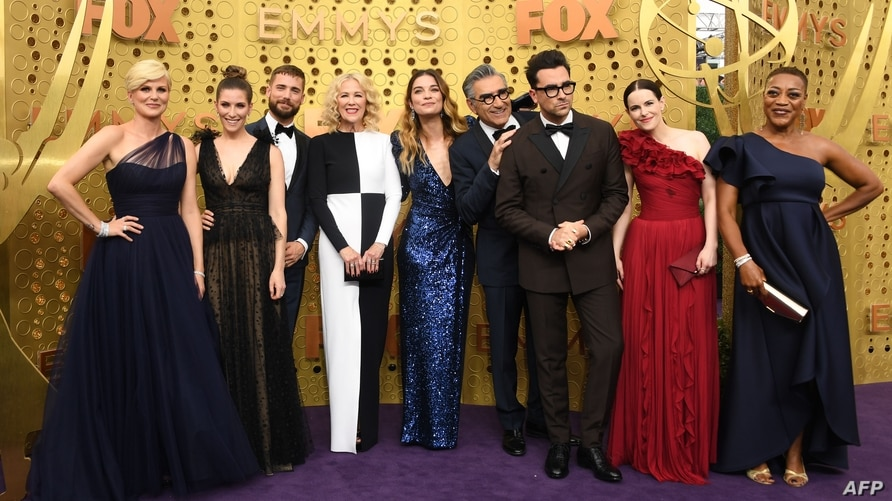 """(FILES) In this file photo taken on September 22, 2019 """"Schitt's Creek"""" cast members arrive for the 71st Emmy Awards at the…"""