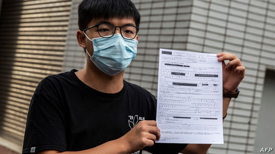 Pro-democracy activist Joshua Wong speaks to the media while holding up a bail document after leaving Central police station in…