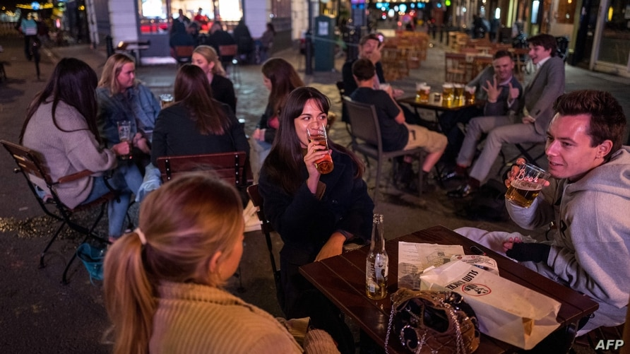 People drink at the outside tables of a bar in Soho, in central London on September 24, 2020, on the first day of the new…