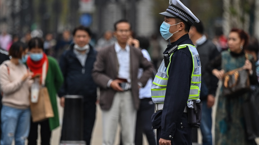 A police officer wearing a face mask monitors pedestrian traffic along a street in Shanghai on October 28, 2020. (Photo by…