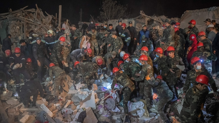 TOPSHOT - Rescue teams work at a site hit by a rocket during fighting over the breakaway region of Nagorno-Karabakh, in the…