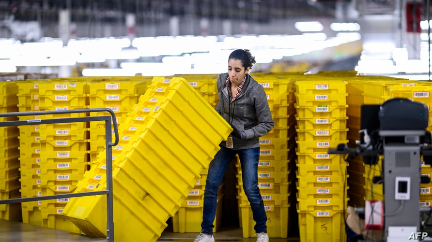 (FILES) In this file photo taken on February 05, 2019, a woman works at a distribution Amazon fulfillment center in Staten…