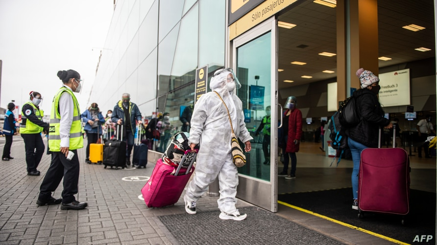 TOPSHOT - A passenger wearing a protective suit and face masks enters to the Jorge Chavez International Airport in Callao, Peru…