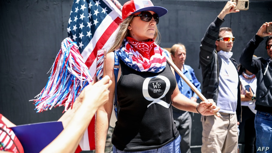 (FILES) In this file photo taken on May 01, 2020 conspiracy theorist QAnon demonstrators protest during a rally to re-open…