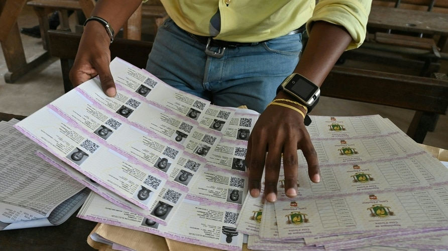 An Ivory Coast Electoral Commission official holds voting cards on October 14, 2020 ,in Abidjan during distribution of voting…