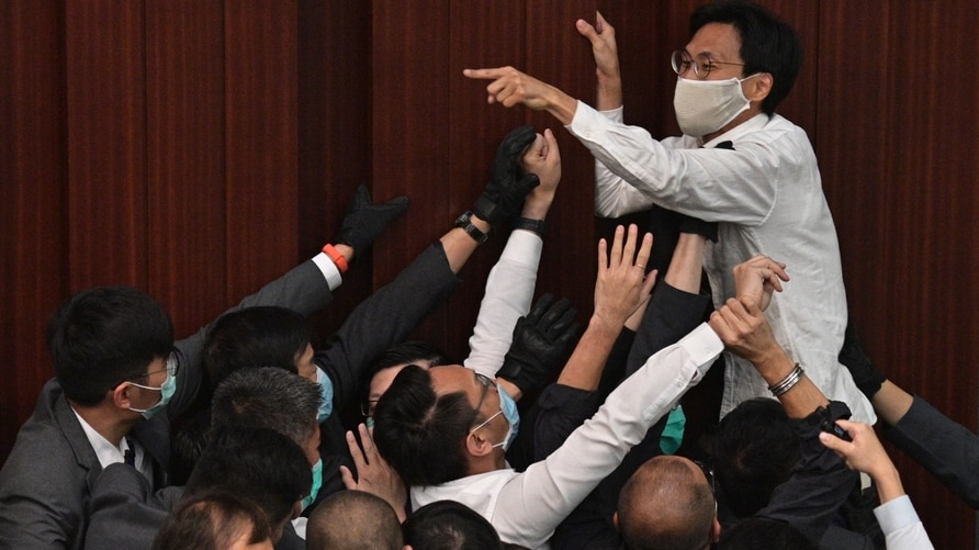 (FILES) In this file photo taken on May 8, 2020, pro-democracy lawmaker Eddie Chu Hoi-dick (top C) shouts at security trying to…