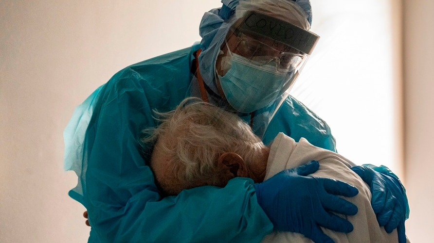 HOUSTON, TX - NOVEMBER 26: (EDITORIAL USE ONLY) Dr. Joseph Varon hugs and comforts a patient in the COVID-19 intensive care…