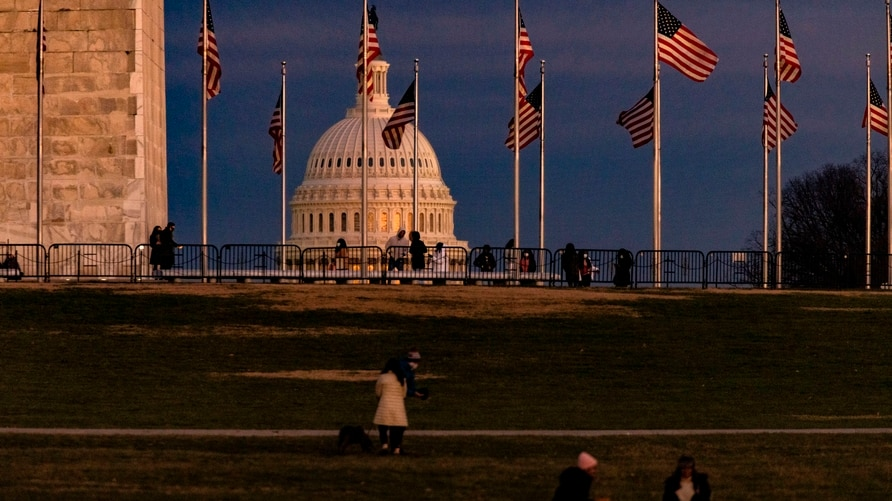 WASHINGTON, DC - DECEMBER 26: The US Capitol Building is seen past the Washington Monument as the sun sets on December 26, 2020…