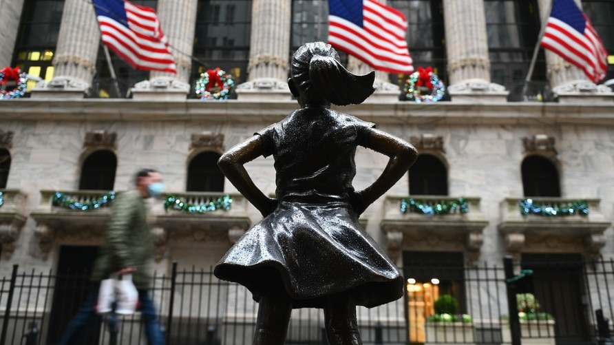 People walk past the New York Stock exchange (NYSE) and 'Fearless Girl' statue at Wall Street after heavy rainfall on November…