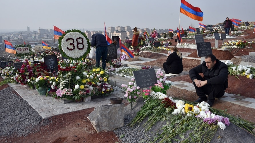 TOPSHOT - People visit the graves of their relatives killed during the Karabakh conflict in Yerevan on December 12, 2020. -…