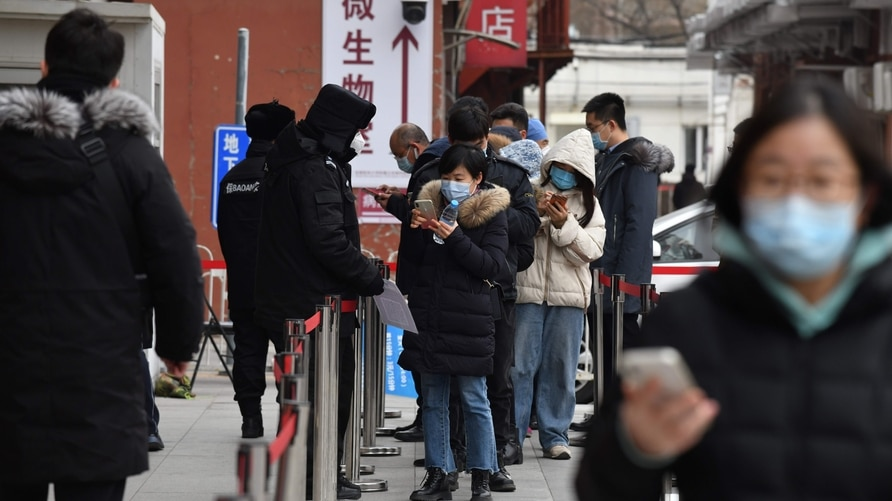 People scan a QR code to display their health code as they line up outside a hospital to get Covid-19 coronavirus tests in…