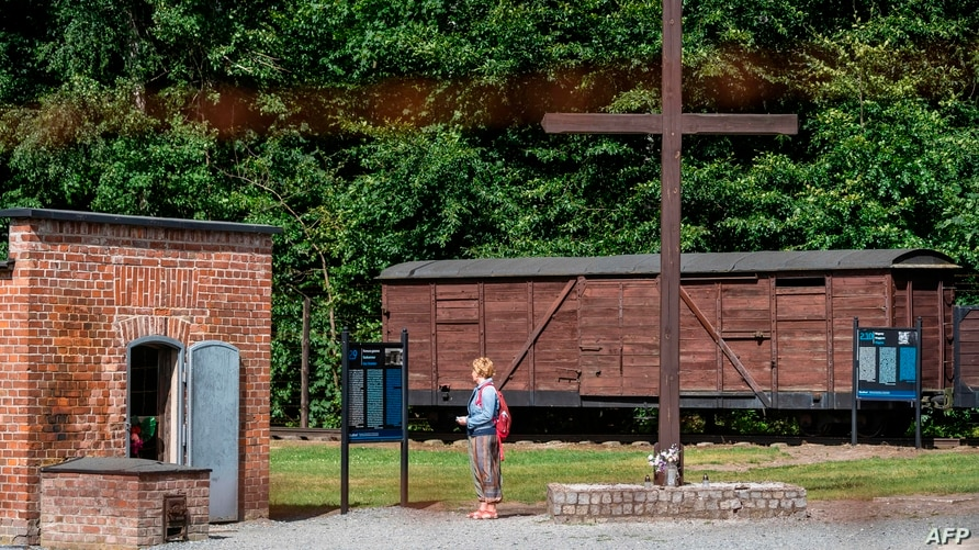(FILES) In this file photo taken on July 21, 2020 a woman is seen next to a gas chamber at the museum of the former Nazi Death…