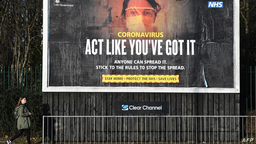 A pedestrian passes a Government Covid-19 information poster near a road in Manchester, northern England, on February 15, 2021…