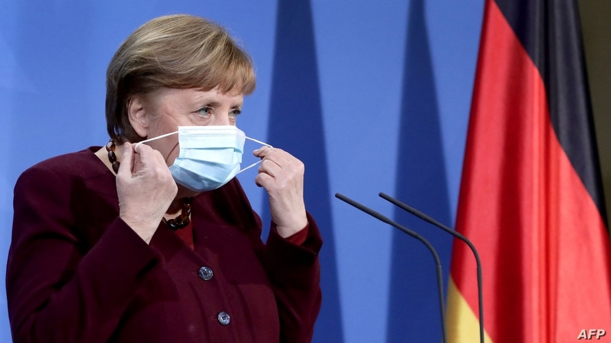 German Chancellor Angela Merkel takes her face mask off as she arrives to a press conference at the chancellery in Berlin,…